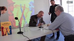 Arturo Pérez Reverte firma el libro.